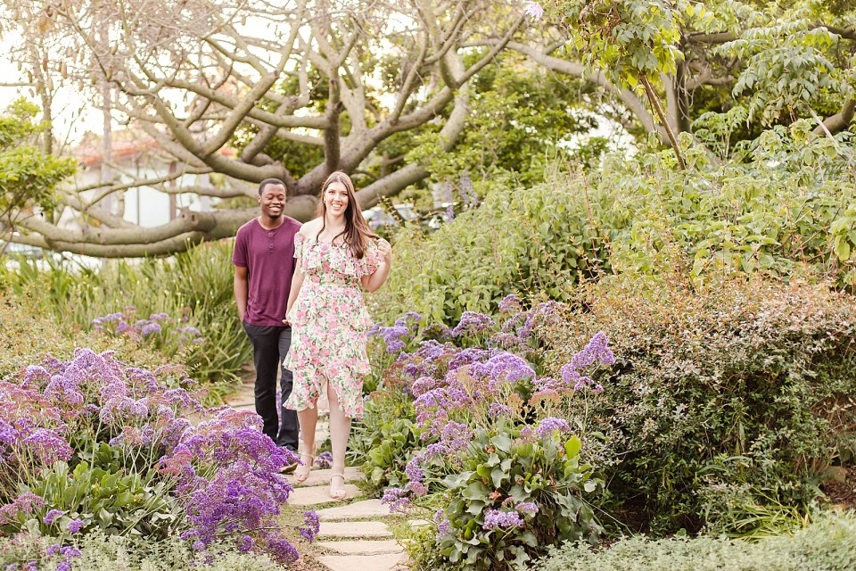 Sarah & Myles walking along a path with purple flowers on each side.