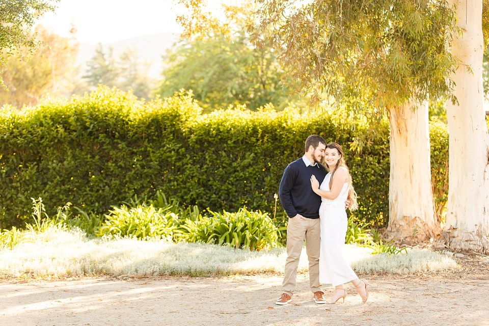 Sofia & Joey are holding each other closely while Sofia smiles at the camera and Joey smiles at Sofia during the couple's Whispering Rose Ranch Engagement session.