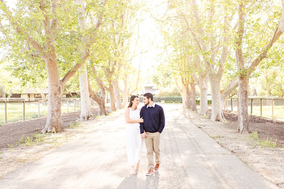 The couple is walking down Sycamore Lane holding hands during their Whispering Rose Ranch Engagement session.