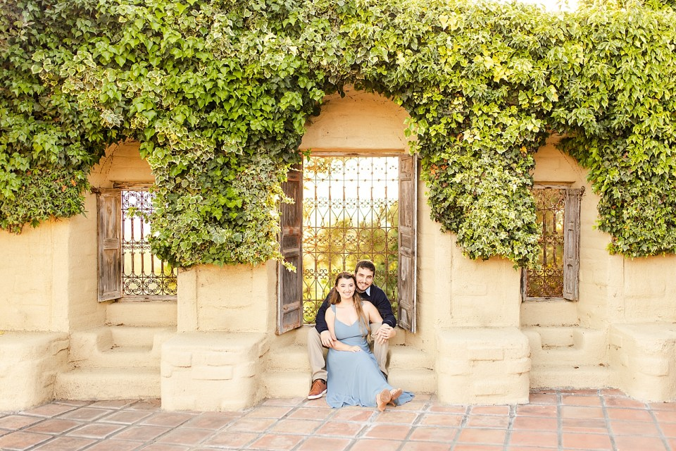 Sofia is wearing a long blue flowy dress and heels. Joey is wearing khakis and a collared shirt with a blue vest and brown shoes. Joey is sitting with his bride in front of him with their backs to a large open window and green leafy vines above their heads.