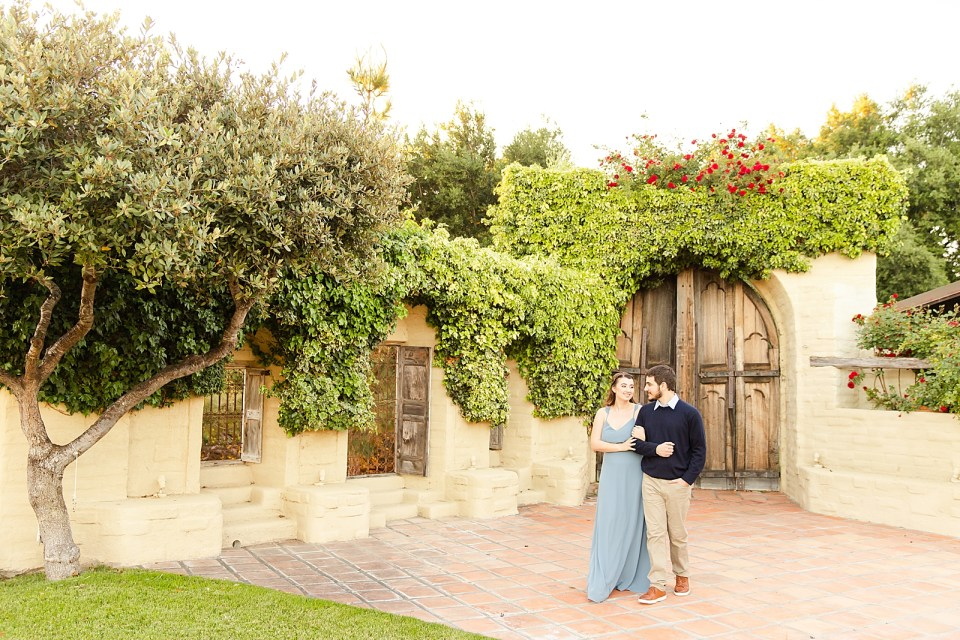 The couple walking arm in arm with the antique doors behind them. They are looking at each other and smiling.