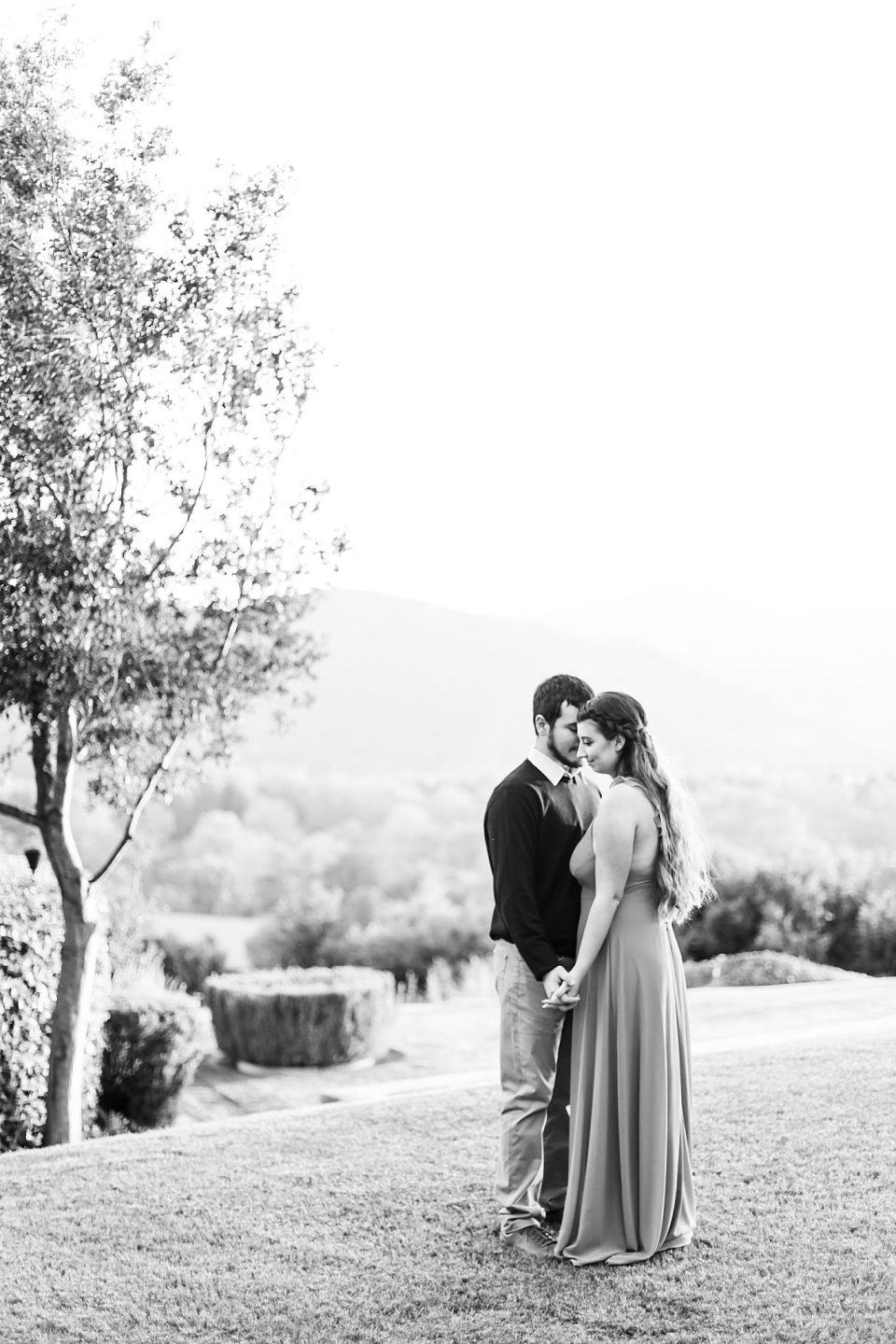 black and white photo of the couple sharing a moment as the sun sets during their Whispering Rose Ranch Engagement Session.