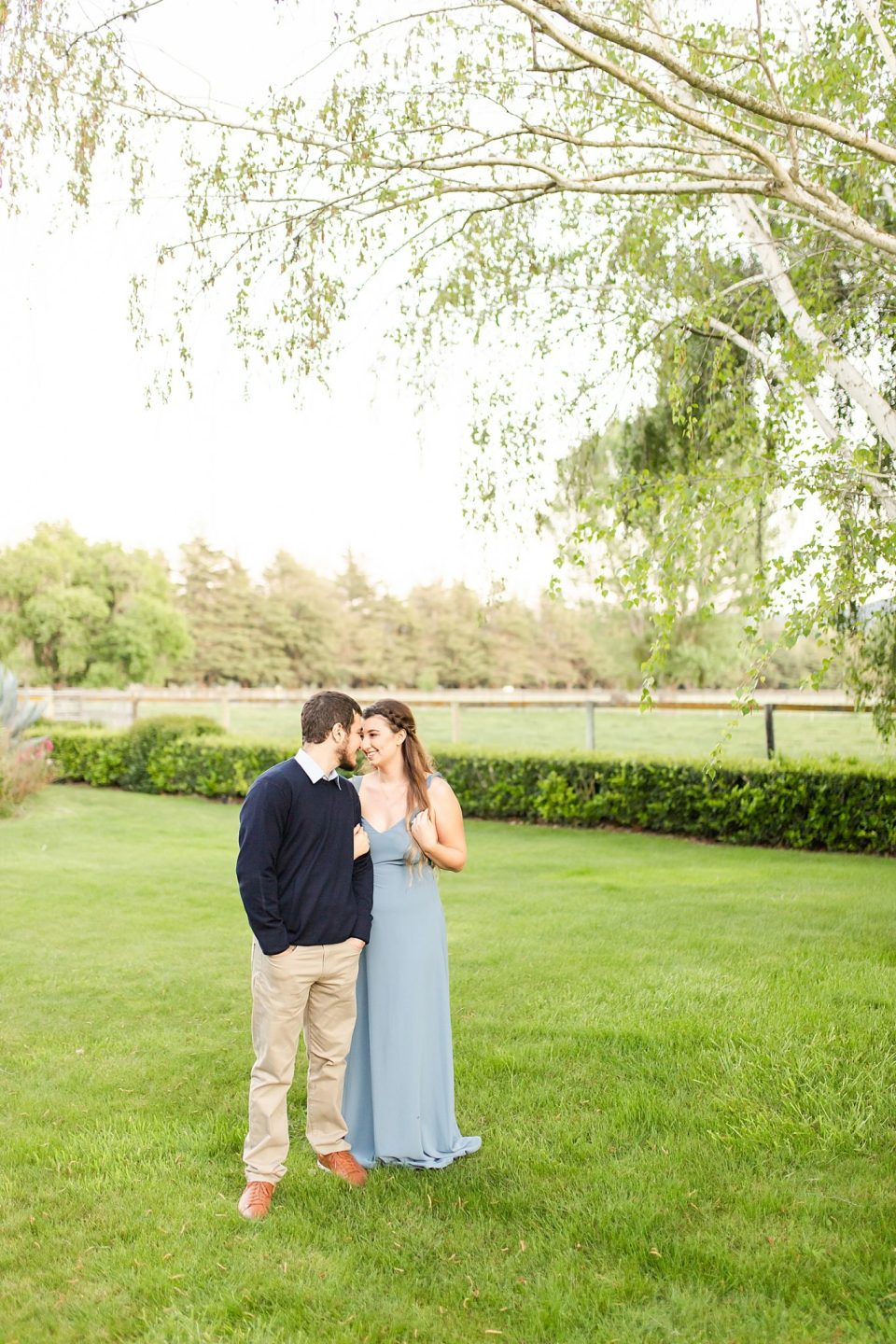 The couple smiling at each other as Sofia holds onto her hair underneath a large tree with enormous branches during their Whispering Rose Ranch Engagement Session.