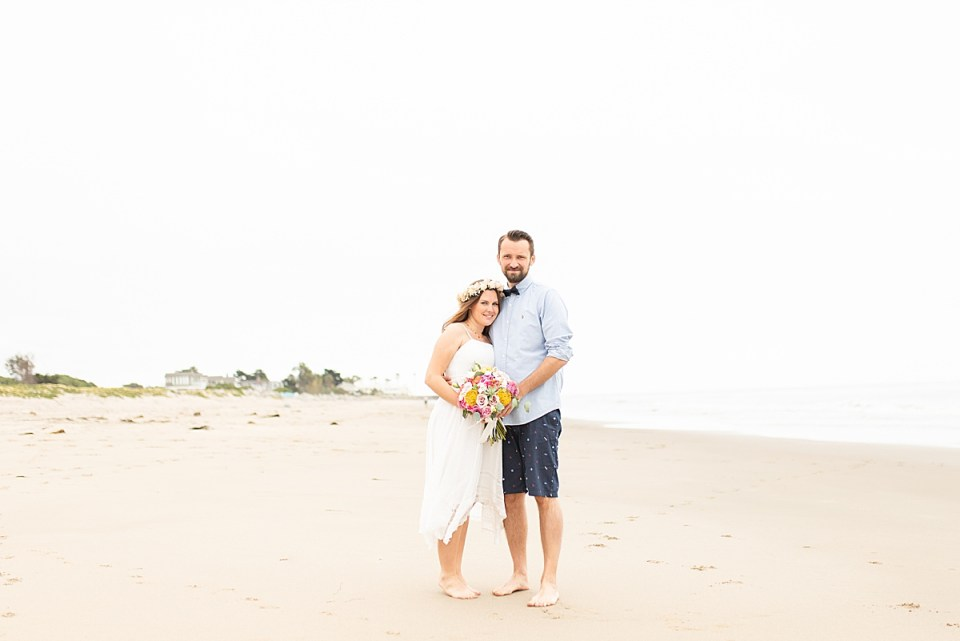The couple smiling at the camera with palm tress behind them in the distance.