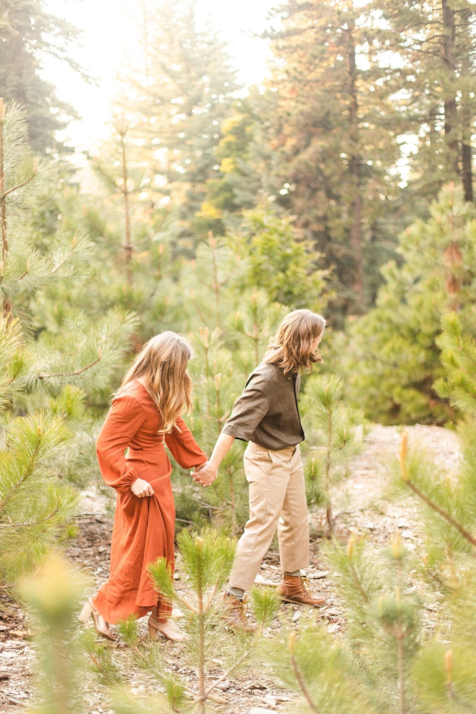 Rothwell leading Abby by the hand deeper into the forest during their Lake Arrowhead Engagement session.