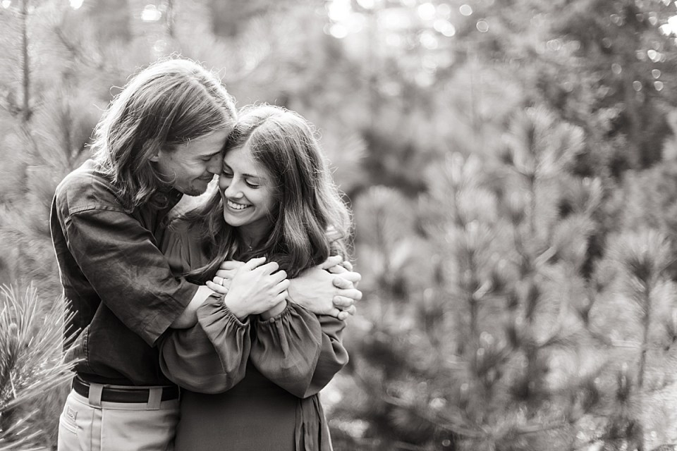 Black and white photo of Rothwell hugging Abby from the side around her shoulders and Abby hugging onto his arms with her hands and both of them are smiling during their Lake Arrowhead Engagement session.