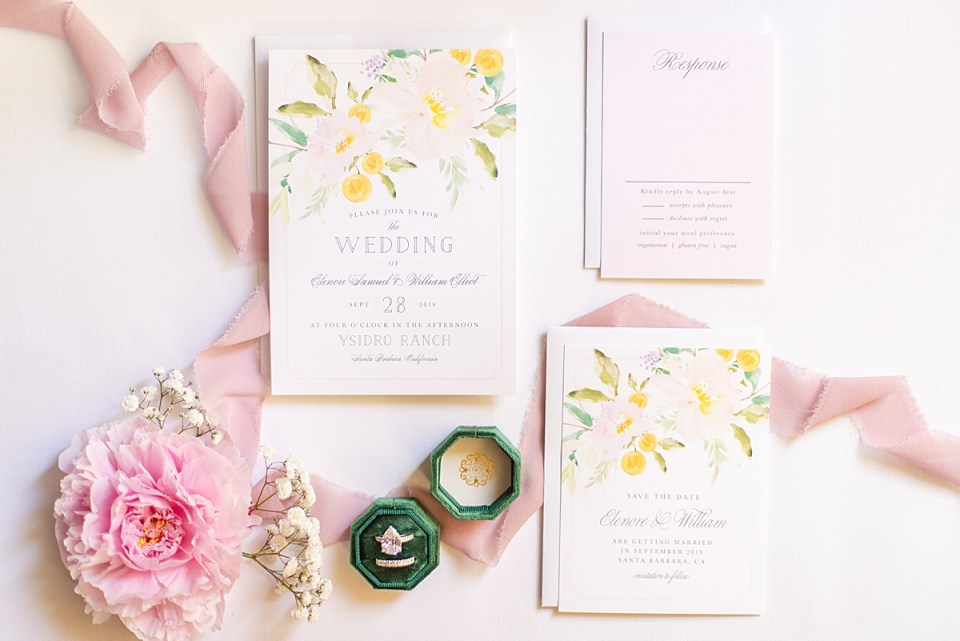 The bride's rings and invitation suite surrounded by florals and greenery.