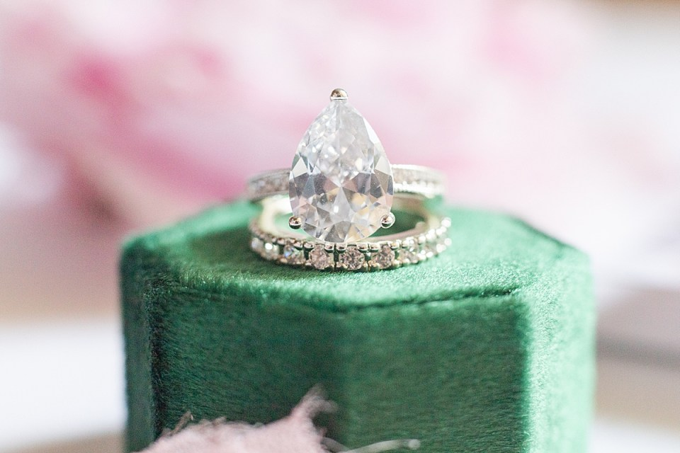 A close up of the bride's rings on an emerald wedding box.