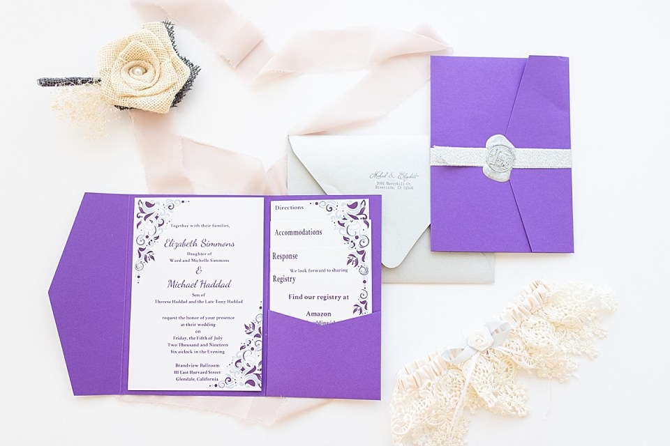 The couple's invitations surrounded by lace, the bride's garter, and Michaels' boutonnière.