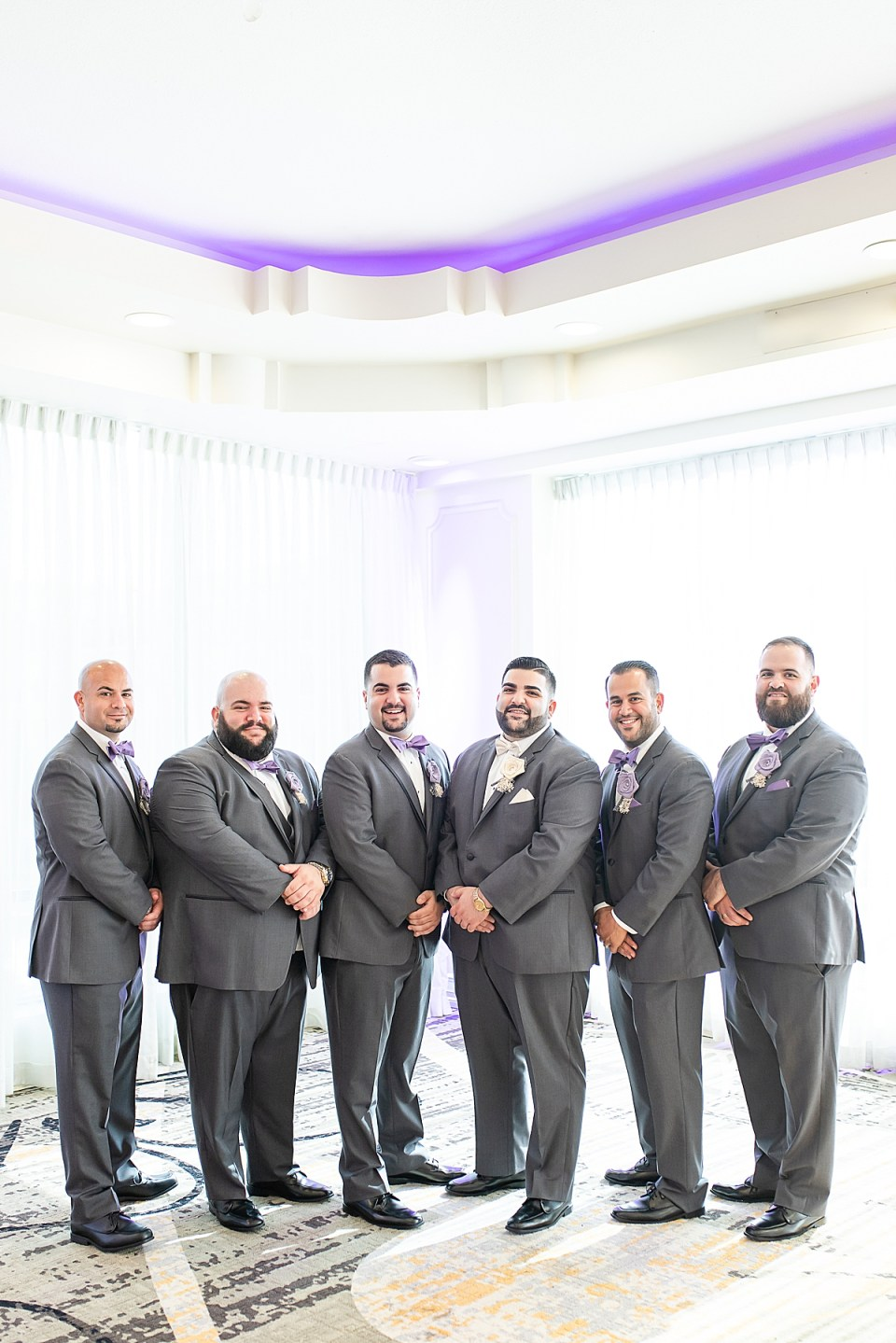 Michael and his groomsmen standing next to each other and smiling at the camera.
