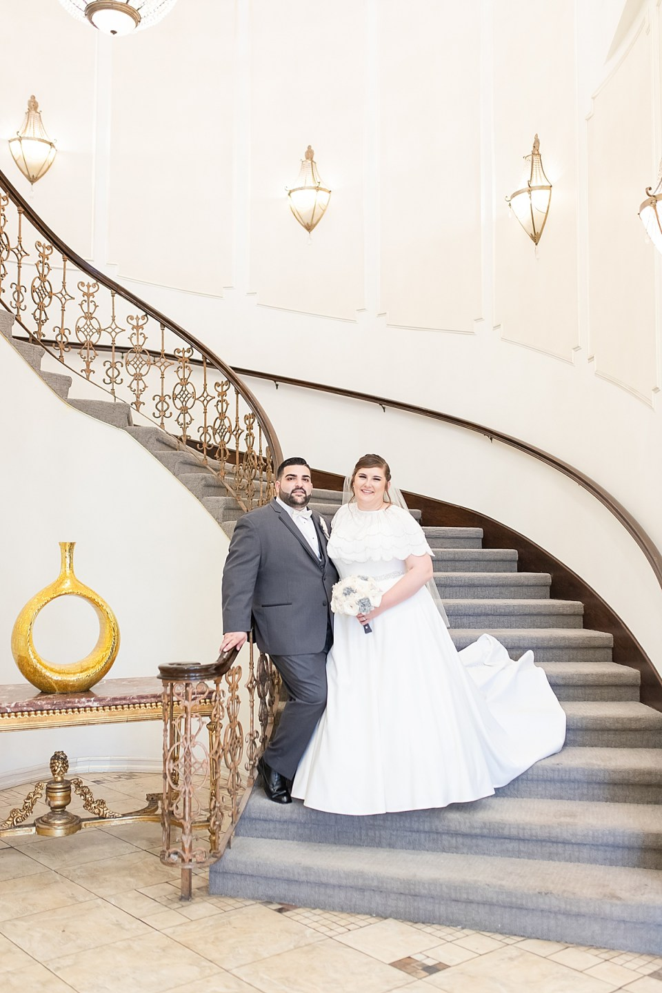 Betsy & Michael smiling at the camera while they stand on the staircase.