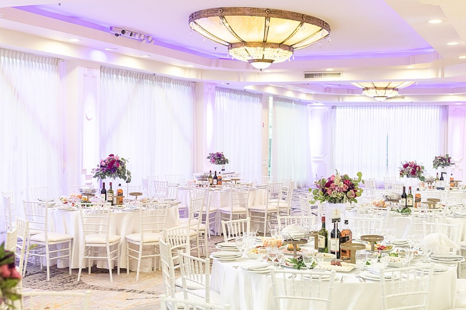 The couples reception decor with food on the tables and purple lighting on the walls.