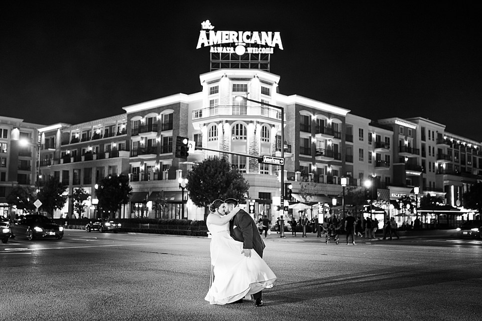 Michael dipping his new wife Betsy in the street outside of the Americana at night.