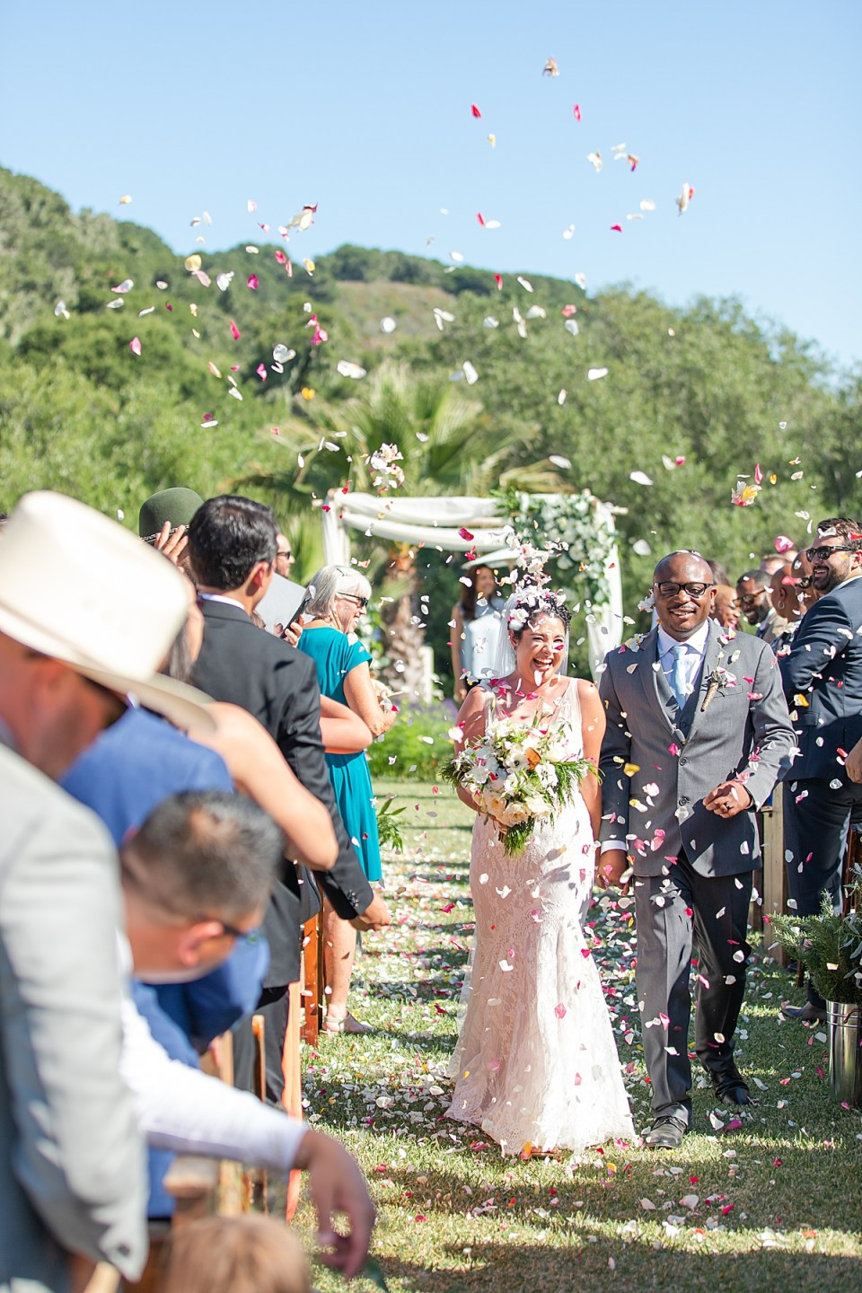 Brandi & Victor coming down the aisle as husband and wife with flower petals in the air thrown by their families at their Rancho San Julian Wedding venue in Santa Barbara county, California.