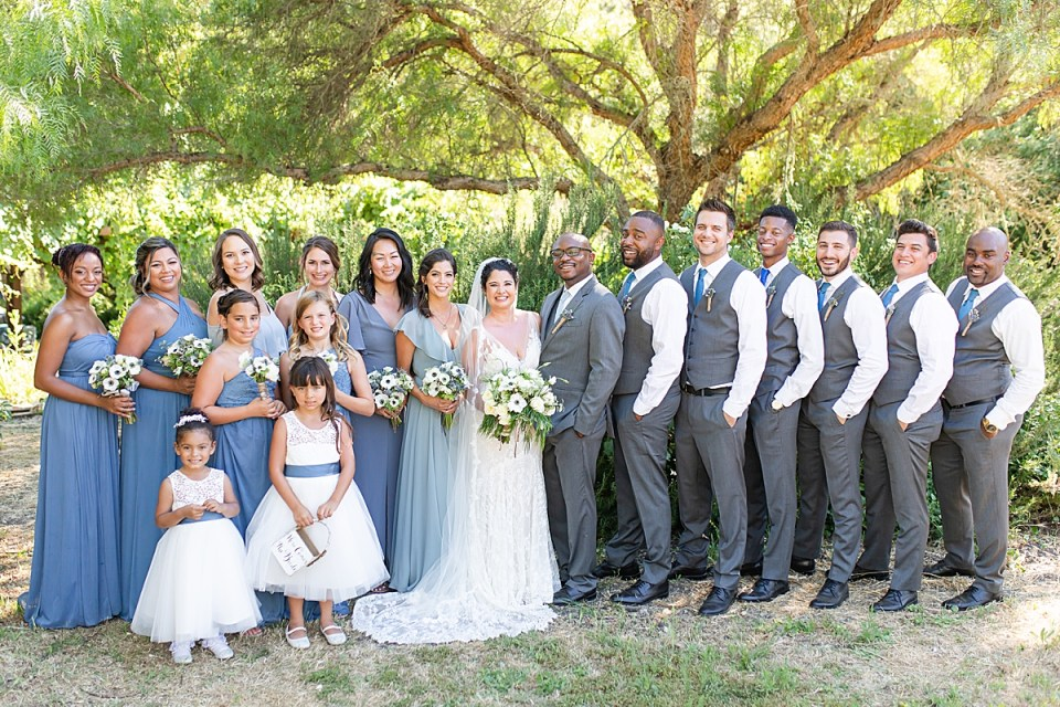 The bride and groom with their full bridal party under a large tree during their bridal party photos as described in their wedding day timeline.