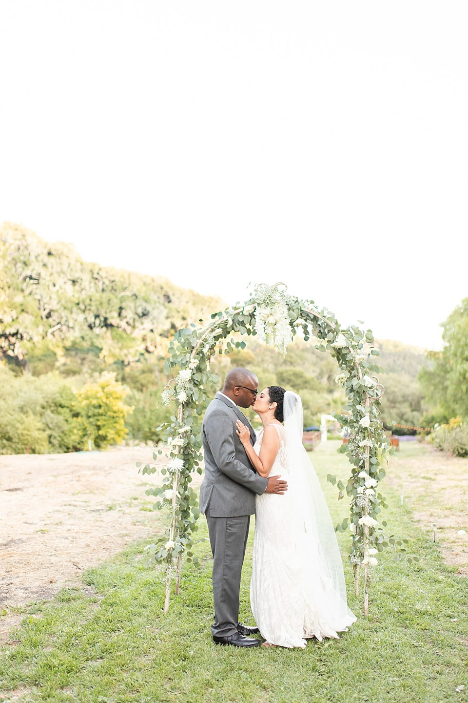 Brandi & Victor sharing a kiss under a trellis filled with flowers and greenery
