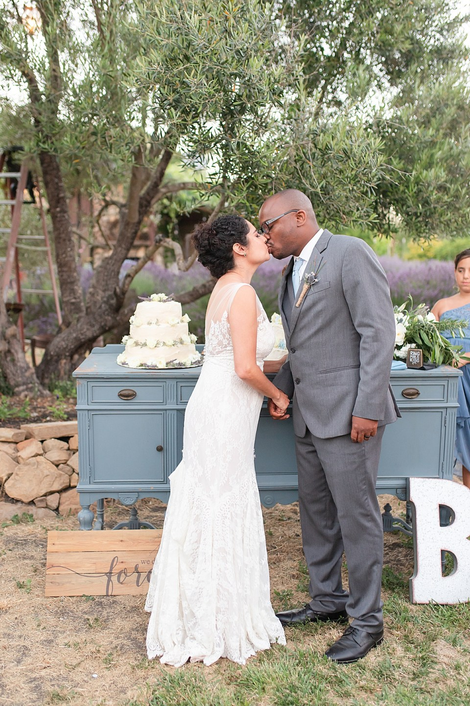 The couple sharing a kiss in front of their wedding cakes during their Rancho San Julian wedding