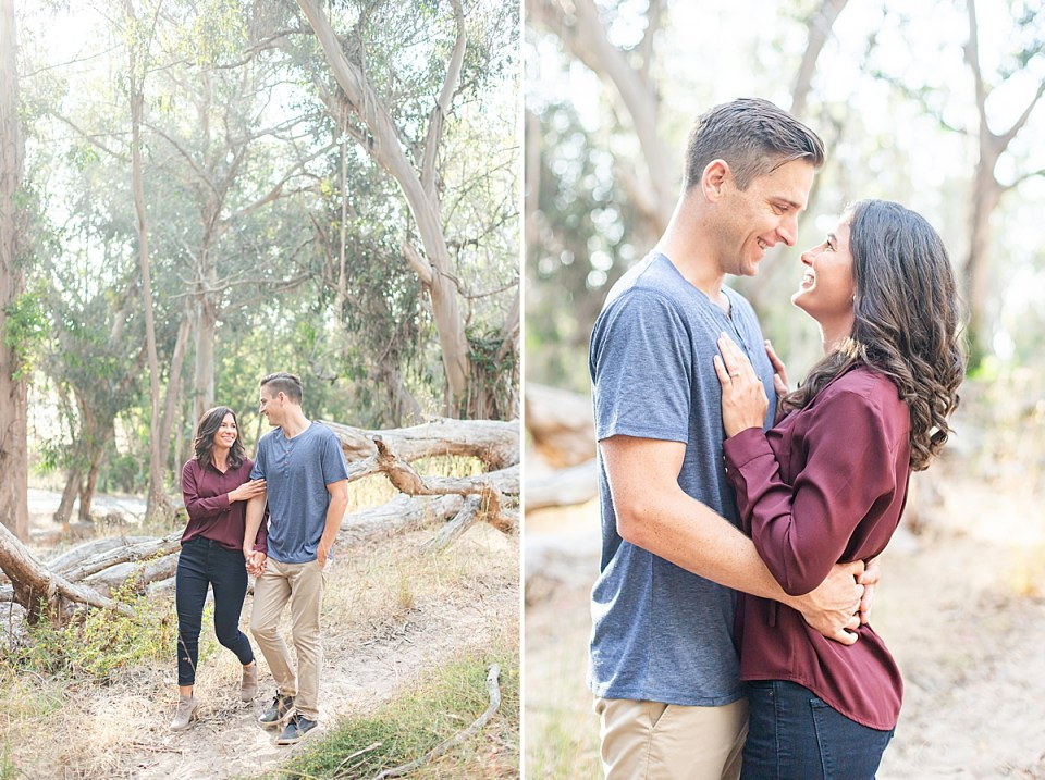 Lauren is wearing a maroon shirt with black pants and booties. She is holding hands with Scott, who is wearing a blue shirt and khakis, and they are surrounded by eucalyptus trees during their Montaña de Oro engagement session.