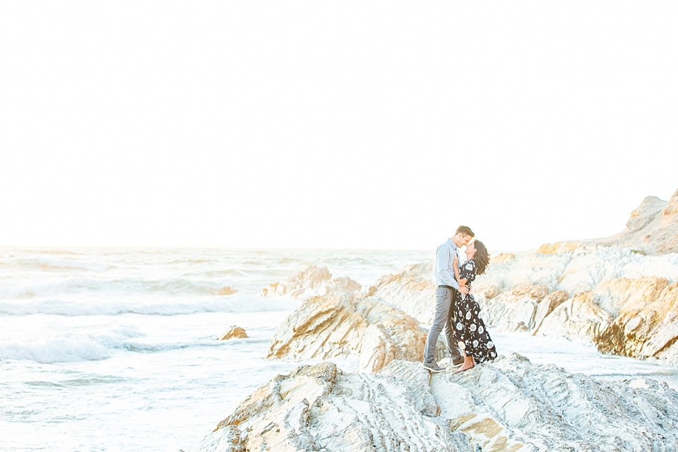 Lauren & Scott standing facing each other with the ocean waves and patches of sunlight behind them.