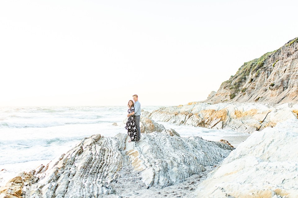 The couple standing on a large rock protruding from the beach with the ocean and bluffs in the background.
