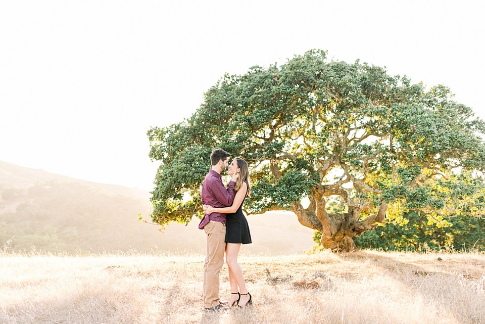 Sunlight shining in through the branches of an oak tree while Kat & Brett stand close together surrounded by light.