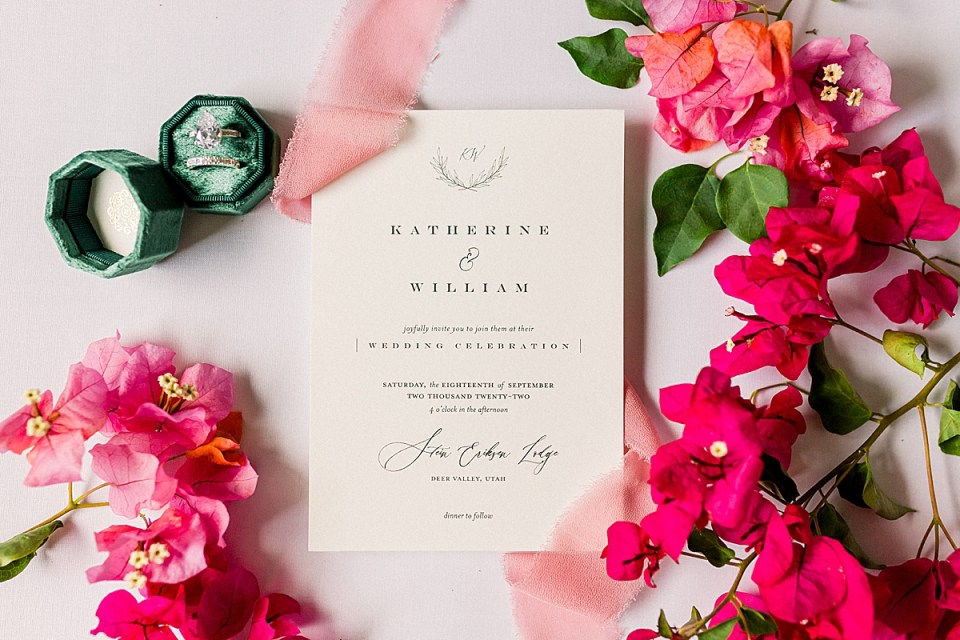 The couple's Wedding Invitations surrounded by red and pink bougainvillea.