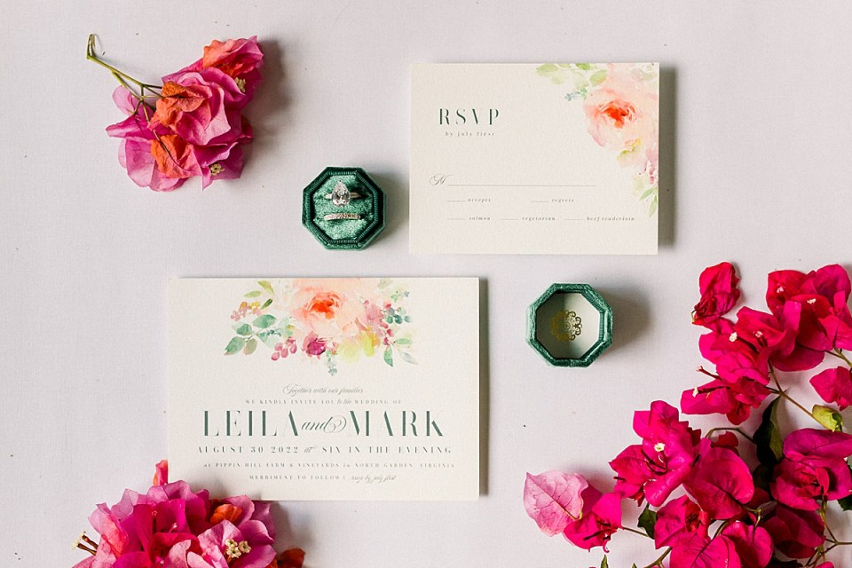 The couple's Wedding Invitations with the green ring box lid and bottom piece holding her rings.