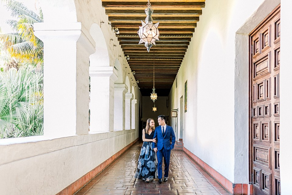 The couple walking down the hallway while giggling and looking at each other during their Santa Barbara Courthouse Engagement session