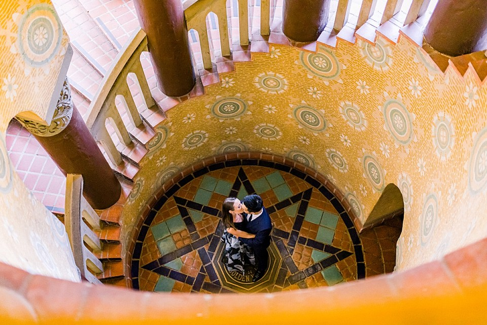 A photo from above the couple as they share a kiss in the middle of the spiral staircase during their Santa Barbara Courthouse Engagement session.
