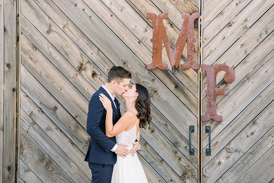 The couple sharing a kiss in front of the barn doors at their wedding venue in San Luis Obispo, California.