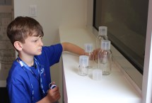 Matthew Lloyd examines Grifols product bottles in the Sterile Filling Facility.