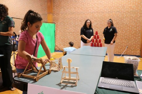 Olivia Preston (front), fourth grade Four Oaks Elementary student, uses the Cups Catapult created by rising South Johnston High seniors Logan Blackmon (right) and Emma Jernigan (left).