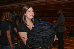 West Johnston High school counselor Rena Keith helps move book bags to the staging area to be transported.