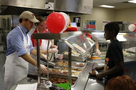 NC Superintendent of Public Instruction Mark Johnson (left) and MCES School Nutrition Manager Tammy Baker (center) serve lunch to George McNeill (right).