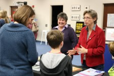 Johnston County Board of Education member Teresa Grant (back left) and local author Sherry Storrs (back, right) discuss books with West Clayton Elementary Principal Paige Barnes (front, left) and Pine Level Elementary student Wilmond Barnes (front, right).