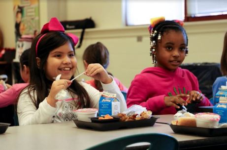 Second grade students Sofia Campos (left) and Haleigh Jones (right) enjoy their school lunch together at Pine Level Elementary.