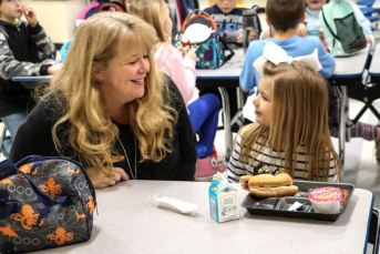Cleveland Elementary Principal Maureen Hanahue (left) and preschool student Peyton Myers have lunch together in the school's cafeteria.