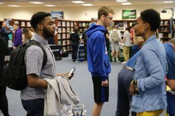 Cleveland High student Jaylen Moss (left) talks with Kendra Arnold (right), Coordinator of Recruiting and Communications for Johnston Community College, at Make a Plan Day.