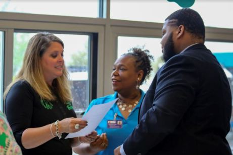 Archer Lodge Middle School Principal Melissa Hubbard (left) and River Dell Elementary Assistant Principal Tandra Batchelor-Mapp (center) talk with Reginald Scott (right), a candidate who attended the job fair.