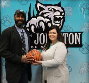 West Johnston High School Principal Jennifer Swartz (right) presents the school's new boys basketball head coach Chucky Brown (left) with a basketball.