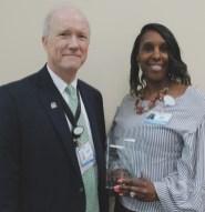 Greg McClain, director of spiritual care and volunteer services, presents the Overa S. Stevens Award for faithful service to chaplain volunteer Iris Hocutt.