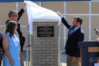 Shelby Bireley (front) looks on as Chad Culver (back, left) and Brett Capps (back, right) unveil the plaque on the Shelby Rose Bireley Agricultural Building.