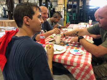 From left, William 'Chris' Wagstaff, Rex Barefoot Jr., Miguel Solgado and Michael Odom enjoy the time they spent painting rocks to donate to children. According to Phillip Knott, plant manager at Champion Hoist and Equipment, the exercise boosts morale.