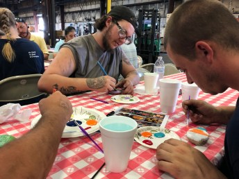 Derrick Maynard, left, and Taylor Upchurch paint rocks to donate to children's organizations in hopes the children will hide them and take joy from finding the rocks. This was a project of Champion Hoist and Equipment in Dunn. Contributed Photo/Jennifer Baker