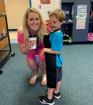 Princeton Elementary student Joseph Heaton-Rhodes (right) serves Princeton Elementary teacher Taylor Adams (left) a cup of coffee from the Pup Cups beverage cart.