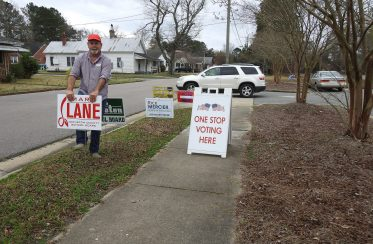School board candidate Mark Lane places one of his signs near the First Baptist Church Ministry Center in Smithfield Thursday morning. The Ministry Center is one of four early voting sites in Johnston County. Early voting began February 13, 2020. JoCoReport.com Photo