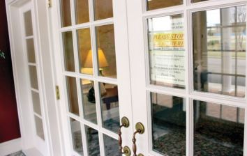 A sign in the vestibule at Skinner & Smith Funeral Home advises visitors to wait for assistance before entering.