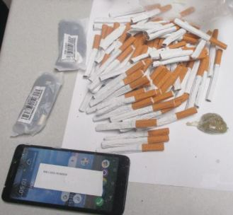 Among the items found in footballs thrown over the fence at Harnett Correctional Institute in Lillington were over 200 loose cigarettes, cellphones and other electronic devices. SUBMITTED PHOTO/NCDPS