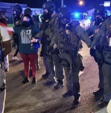 Johnston County Sheriff STAR/SWAT team officers hold hands and pray with protesters in the middle of Highway 301 in Selma Sunday night. Facebook photo
