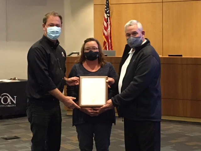 """(L to R): Clayton Mayor Jody McLeod presents Browder family members Lisa Ferguson and Jason Browder with a framed copy of the resolution to rename the Greenway bridge for their father James """"Skip"""" Browder."""
